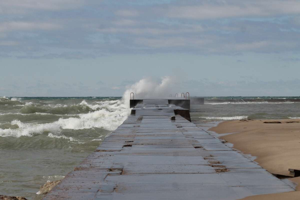 Waves crash over the First Street Pier in Manistee on Thursday.