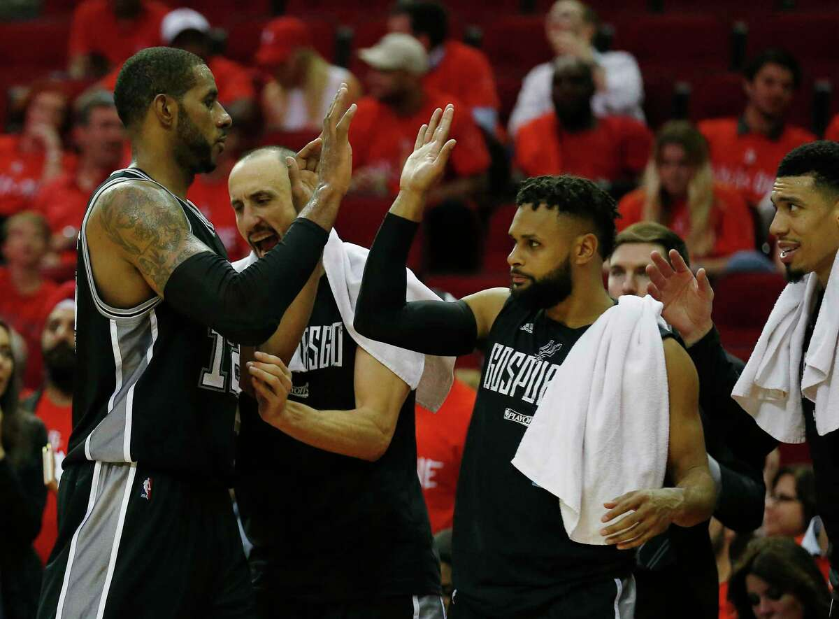 Spurs' LaMarcus Aldridge (12) gets congratulated by teammates Manu Ginobili (20) and Patty Mills (08) as he heads to the bench in the game against the Houston Rockets in Game 6 of the Western Conference semifinals at the Toyota Center on Thursday, May 11, 2017. Spurs defeated the Rockets, 114-75, to win the series and advance to the Western Conference Finals against the Golden State Warriors. (Kin Man Hui/San Antonio Express-News)