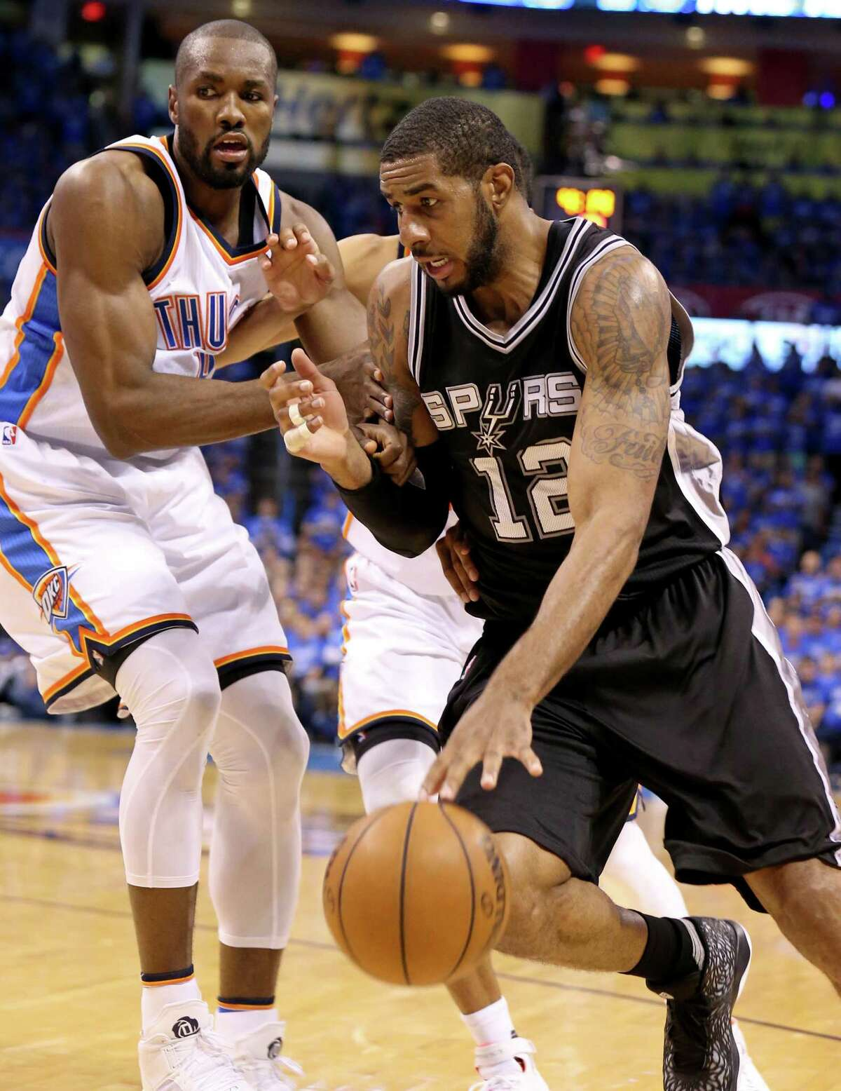 San Antonio Spurs' LaMarcus Aldridge looks for room around Oklahoma City Thunder's Serge Ibaka during first half action of Game 6 in the Western Conference semifinals Thursday May 12, 2016 at Chesapeake Energy Arena in Oklahoma City, Oklahoma.