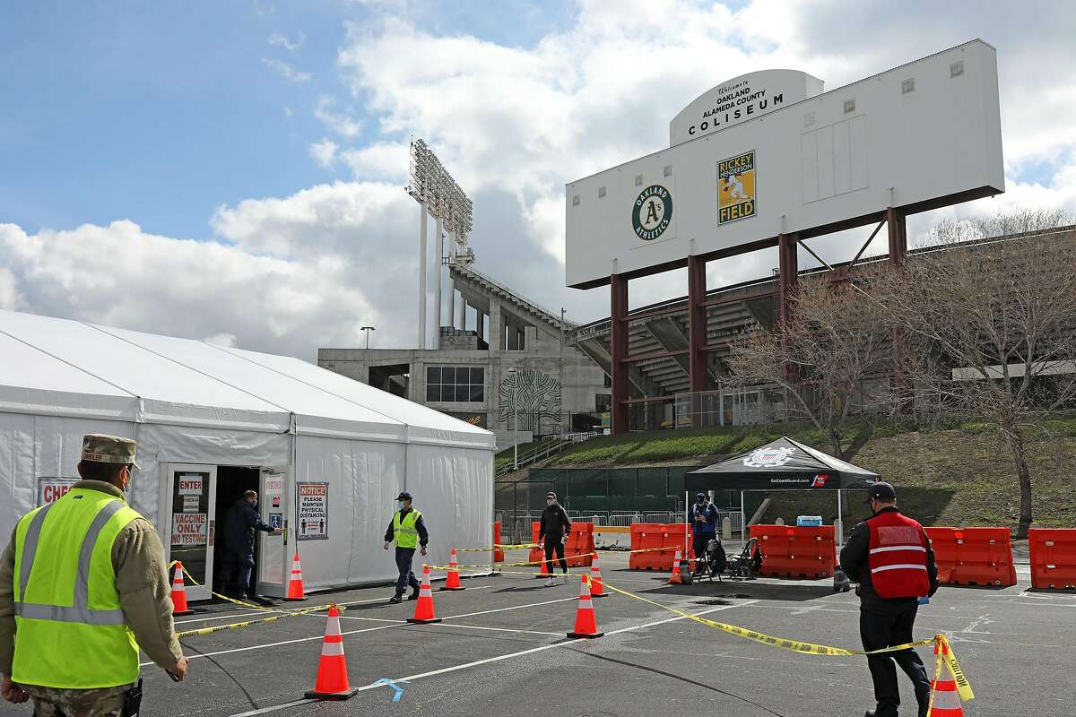 Military members enter a vaccination tent at the Oakland Coliseum in March.