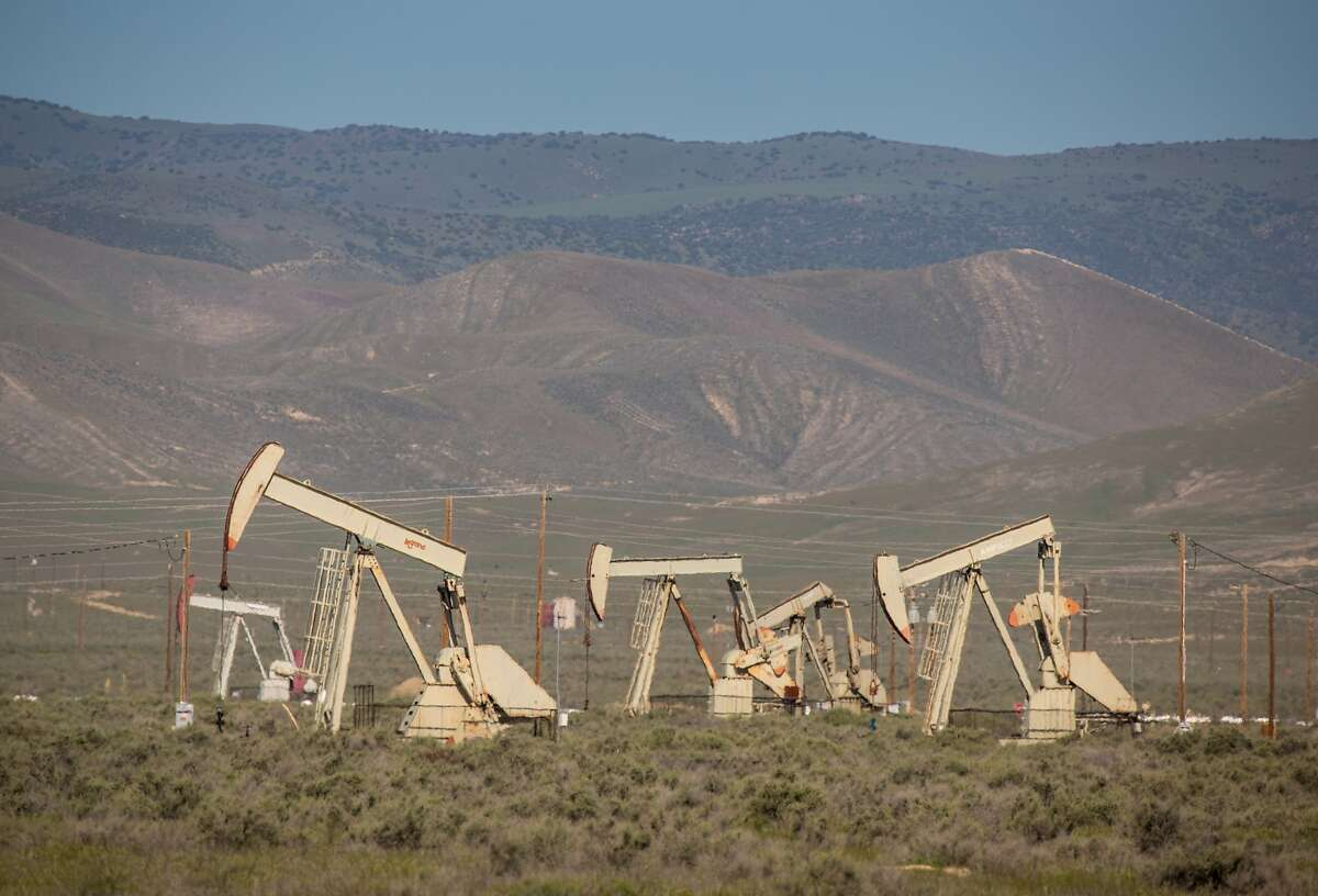 Oil pumping rigs and transmission lines dot the landscape along Highway 33. Kern County has approved a policy to streamline approvals, potentially allowing 2,700 oil and gas wells annually.