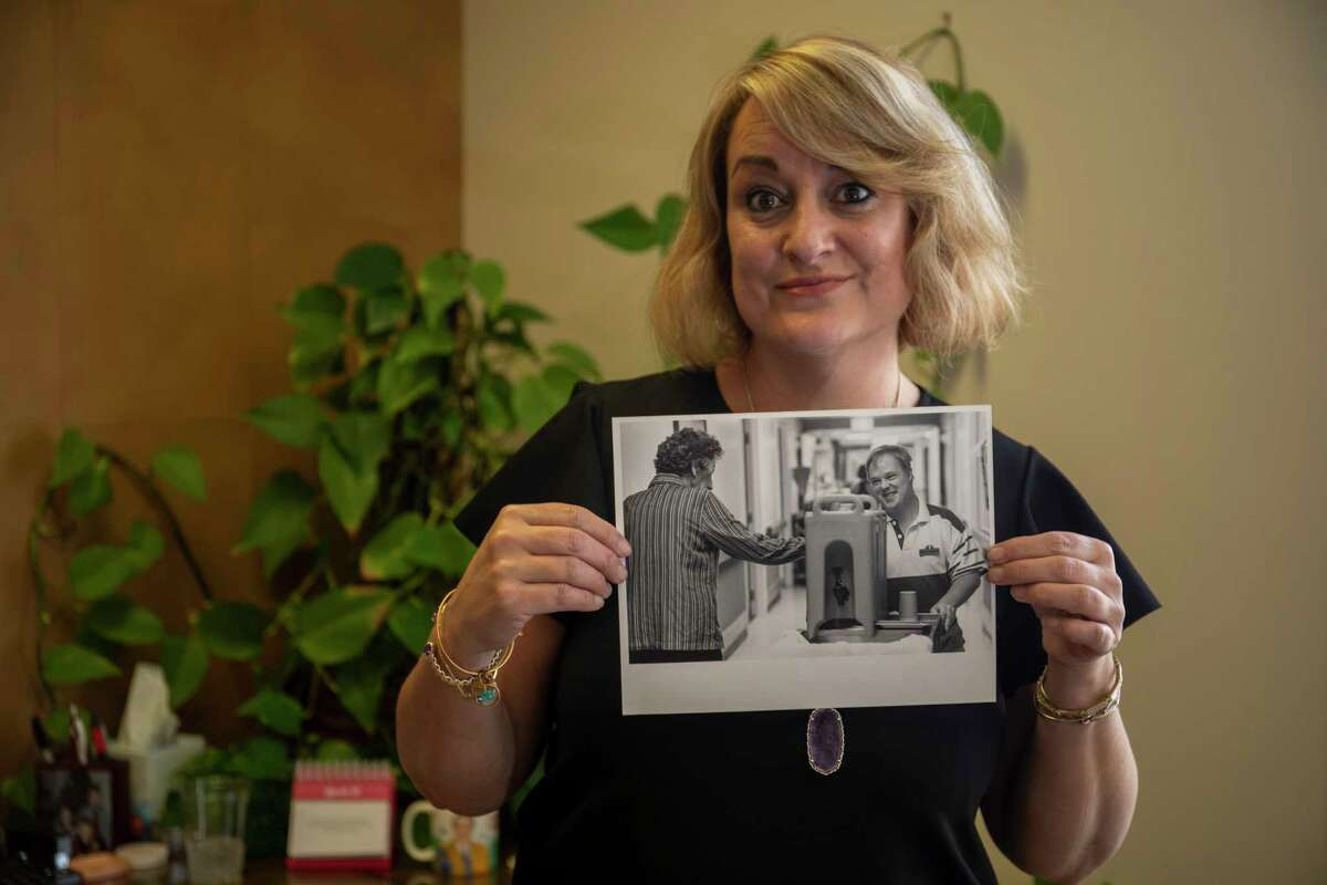 Kathleen Kirwan-Haynie holds up a picture of her brother Daniel Kirwan of him volunteering at a nursing home as seen Thursday, March 11, 2021 at Senior Life Midland. Jacy Lewis/ Reporter-Telegram