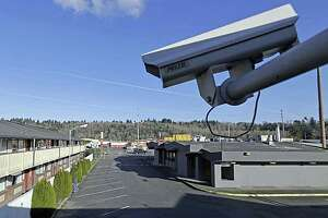 In this March 4, 2020 photo, a security camera is shown on the second floor of a row of rooms at a motel in Kent, Wash. Hackers aiming to call attention to the dangers of mass surveillance said they were able to peer into hospitals, schools, factories, jails and corporate offices after they broke into the systems of a security-camera startup. That California startup, Verkada, said Wednesday it is investigating the scope of the breach, first reported by Bloomberg, and has notified law enforcement and its customers.