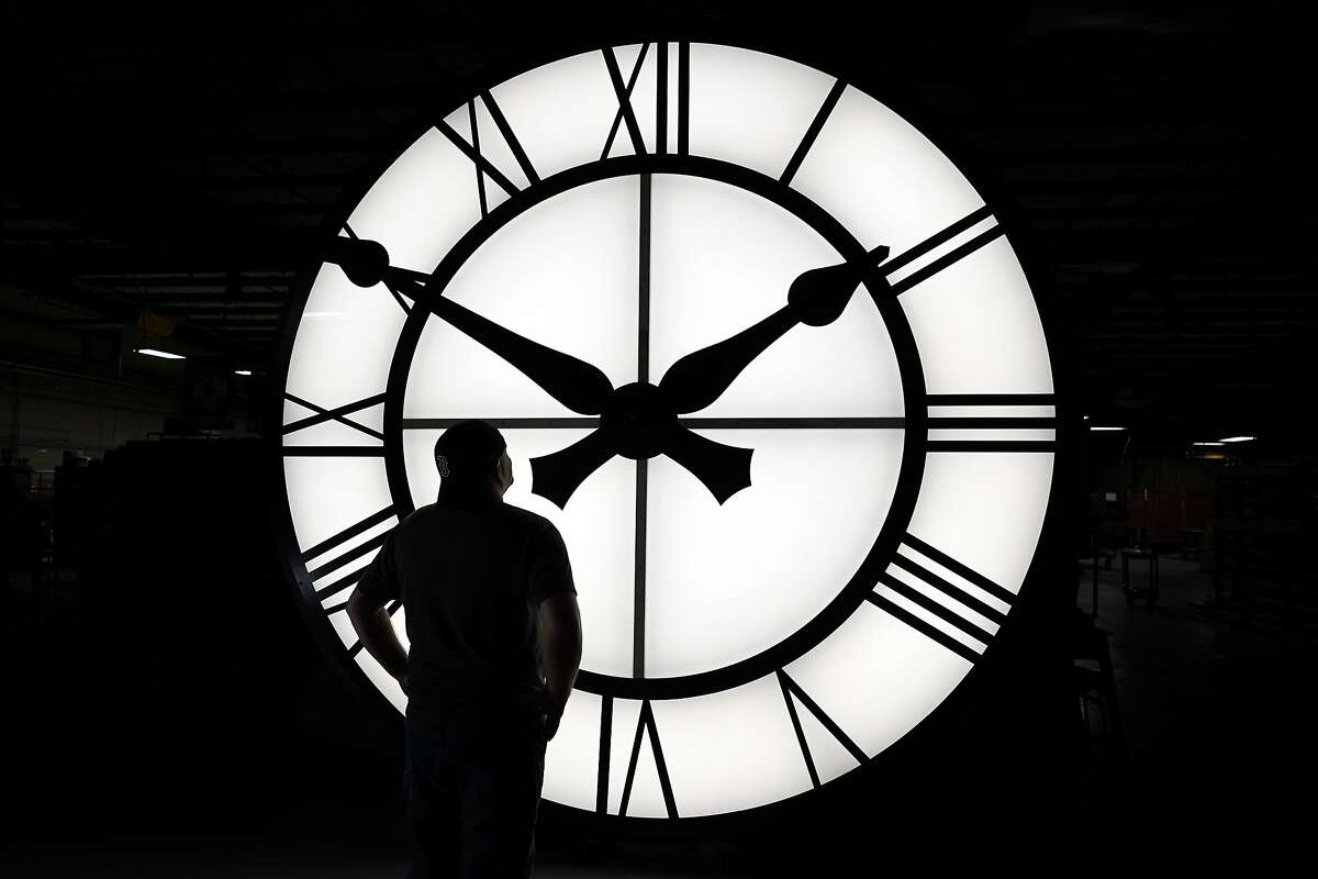 Electric Time technician Dan LaMoore admires a 1000-lb., 12-foot diameter clock constructed for a resort in Vietnam, Tuesday, March 9, 2021, in Medfield, Mass. Daylight saving time begins at 2 a.m. local time Sunday, March 14, 2021, when clocks are set ahead one hour. (AP Photo/Elise Amendola)