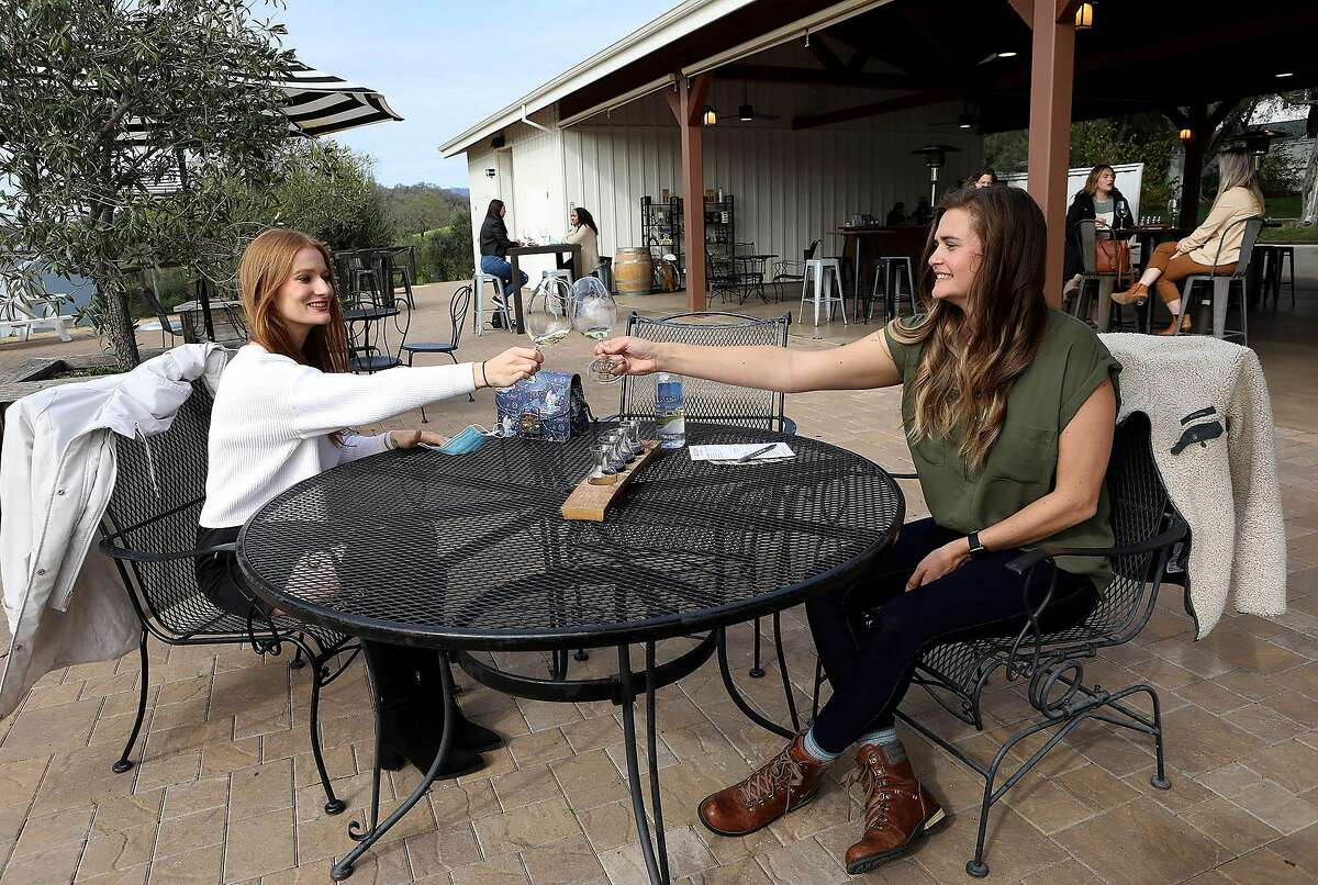 Mary Ann Martin, left, and Brittani Markowski clink their glasses as they prepare to drink wine at BR Cohn Winery on Thursday, January 18, 2021, in Glen Ellen, Calif. Vintage Wine Estates is a wine company that's planning a public offering this spring. The company owns about 50 wine brands, and one of them is B.R. Cohn in Glen Ellen.