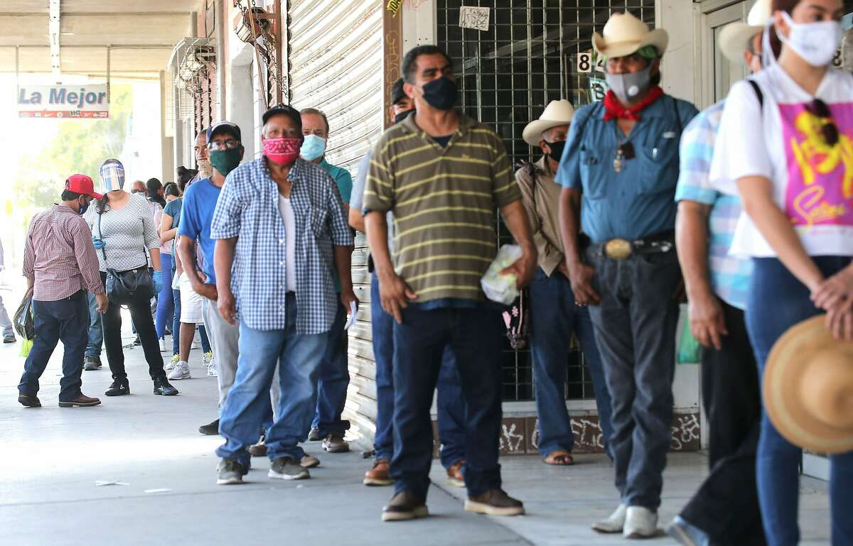 A crowd lines up for unemployment claims outside a bookkeeping shop in El Centro in July.