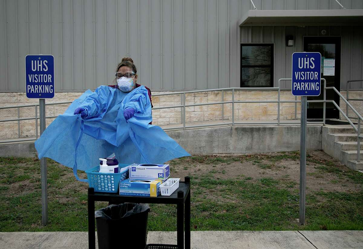 Medical Assistant Crystal Casias removes her gown after testing a woman who remained in her car, for COVID-19 at University Health's Southwest ISD School-based Health Clinic in San Antonio on Wednesday, Feb. 10, 2021.