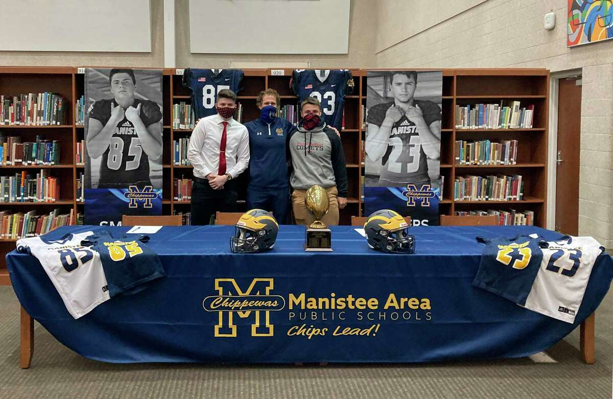 Manistee's Eric Smith (left) and Landen Powers (right) are joined by Chippewa football coach Troy Bytwork at a signing ceremony this week. The two will play football for Olivet College next year. (Dylan Savela/News Advocate)