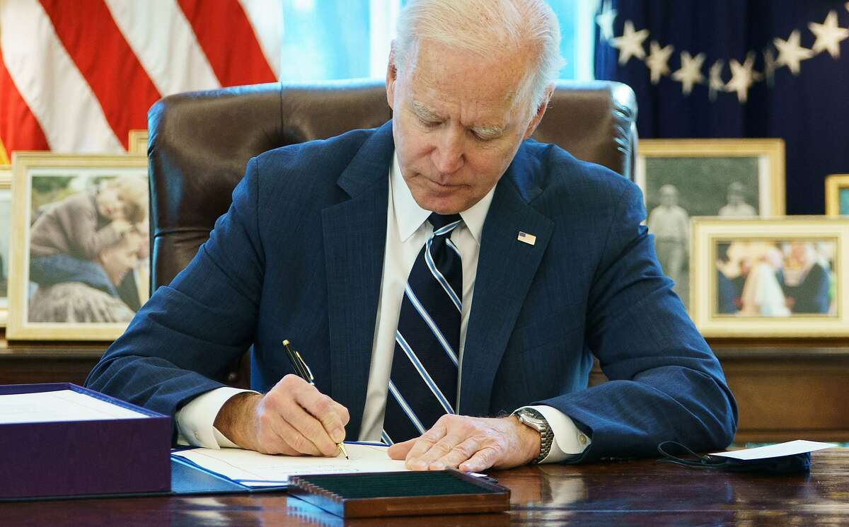 President Joe Biden signs the American Rescue Plan on March 11, 2021, in the Oval Office of the White House in Washington, D.C. Biden signed the $1.9 trillion economic stimulus bill and will give a national address urging hope on the first anniversary of the start of the coronavirus pandemic. (Mandel Ngan/AFP/Getty Images/TNS)