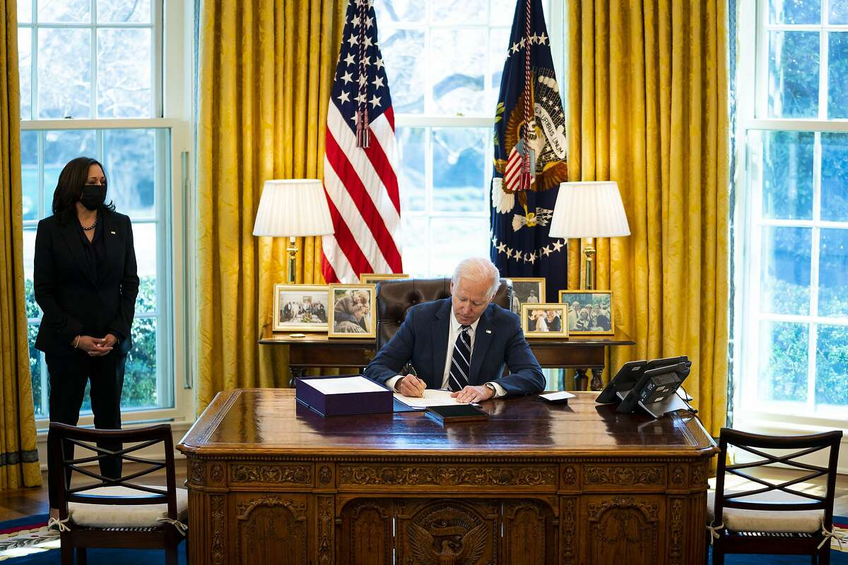 """President Joe Biden signs the """"American Rescue Plan"""" as Vice President Kamala Harris looks on in the Oval Office of the White House in Washington on Thursday, March 11, 2021, a day earlier than the White House had planned, ushering in new federal aid across the country amidst the coronavirus pandemic. (Doug Mills/The New York Times)"""