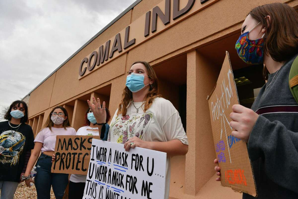 New Braunfels Canyon High School students listen Thursday to junior Reyna Dews, center, during a protest of the Comal ISD board's decision to make masks optional.