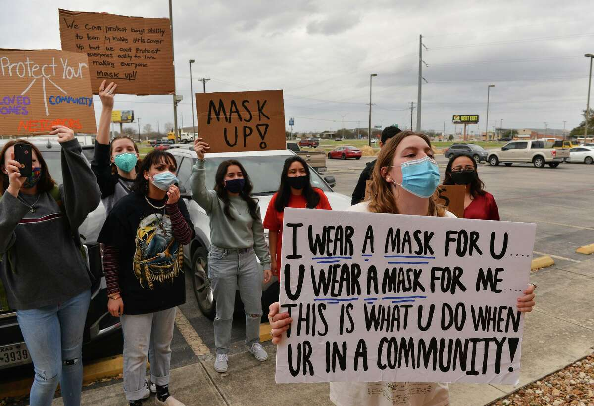 New Braunfels Canyon High students protest Thursday evening in front of the school. They called on the board to reconsider its decision on making masks optional.