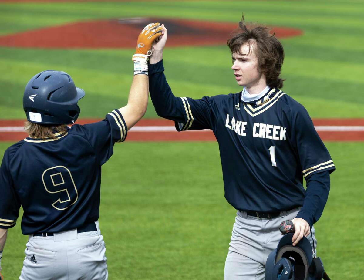 Shane Sdoa (1) of Lake Creek and Jaron Lyness (9) high hive one another after Sdoa hit a home run during the fourth inning of a Baseball Tournament at Grand Oaks High School, Thursday, March 11, 2021 in Spring.