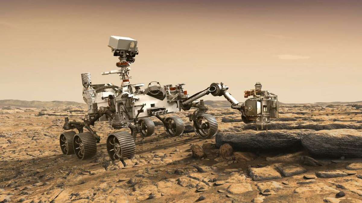 In this illustration made available by NASA, the Mars 2020 rover studies a Mars rock outrcrop.