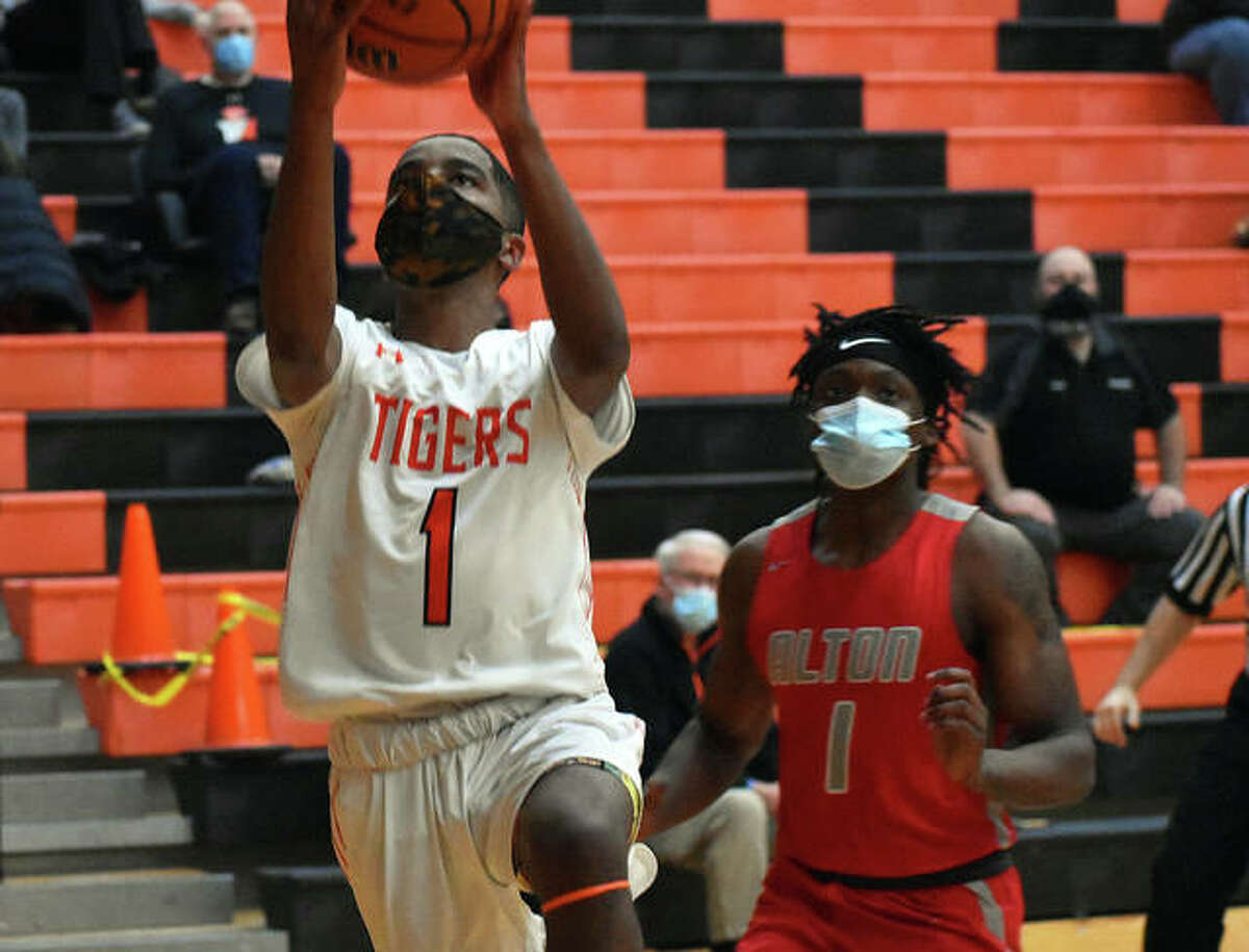 Edwardsville senior Caleb Valentine goes up for a lay-in with Alton's Ja'Markus Gary trailing him on the play in the first half of Thursday's game inside Lucco-Jackson Gymnasium.