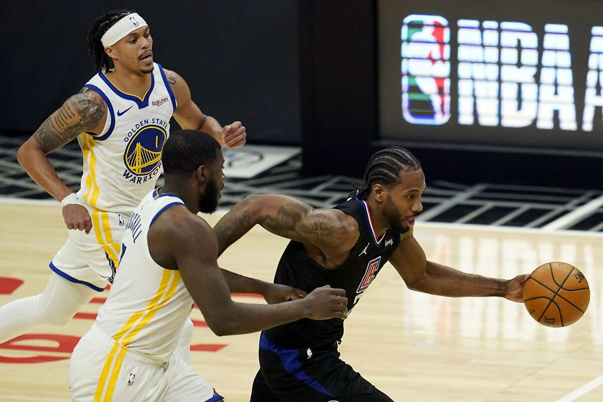 Los Angeles Clippers forward Kawhi Leonard, right, dribbles past Golden State Warriors forward Eric Paschall, bottom left, and Damion Lee (1) during the second half of an NBA basketball game Thursday, March 11, 2021, in Los Angeles. (AP Photo/Marcio Jose Sanchez)