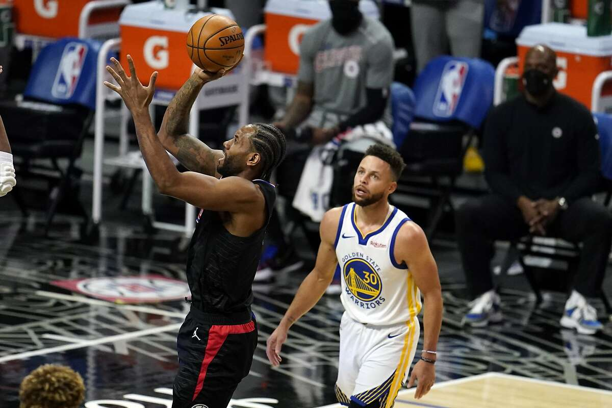Los Angeles Clippers forward Kawhi Leonard, left, shoots past Golden State Warriors guard Stephen Curry during the first half of an NBA basketball game Thursday, March 11, 2021, in Los Angeles. (AP Photo/Marcio Jose Sanchez)