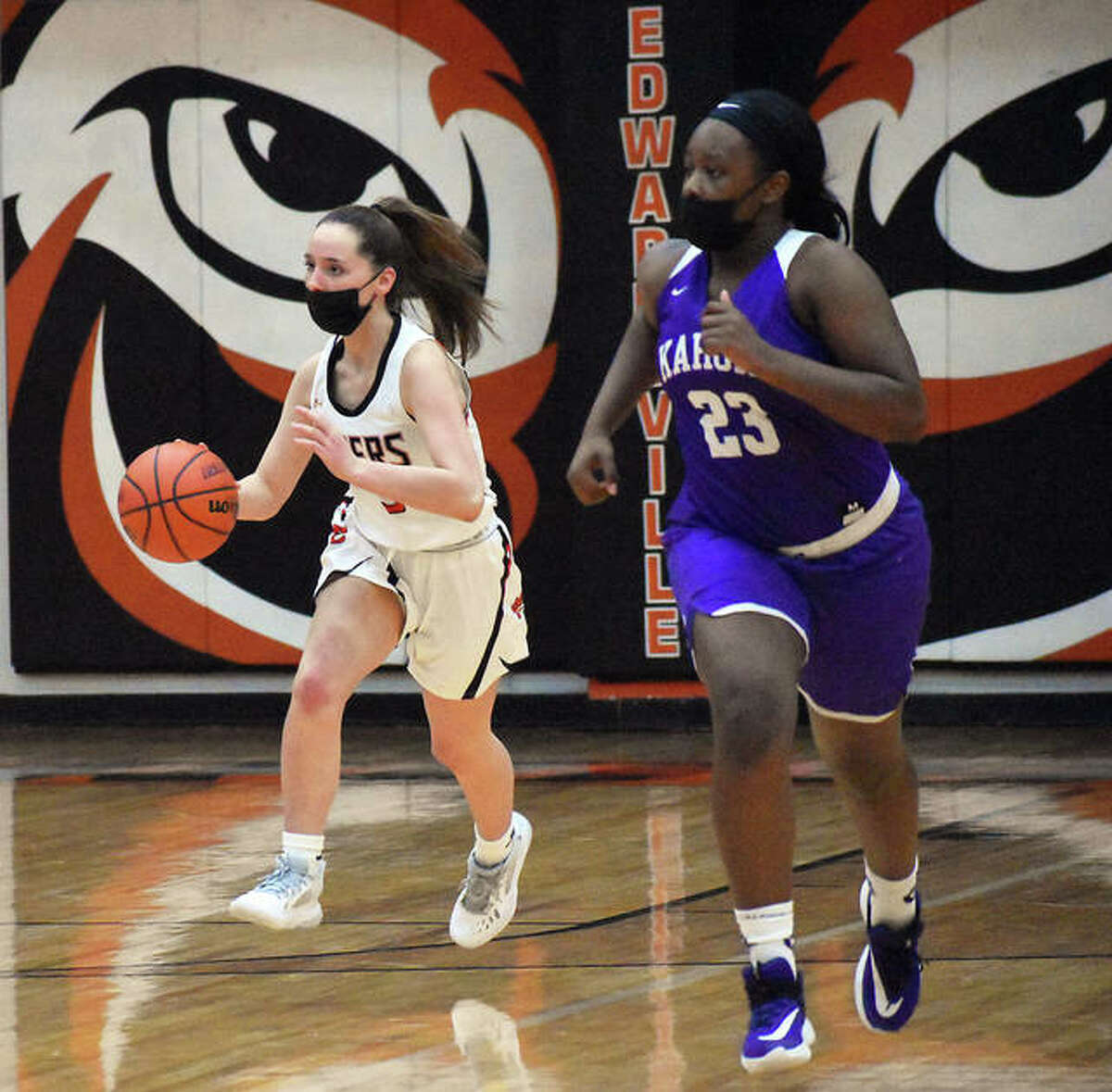 Edwardsville guard Gwen Anderson, left, brings the ball up the court for the Tigers in the fourth quarter of Thursday's game against Collinsville.