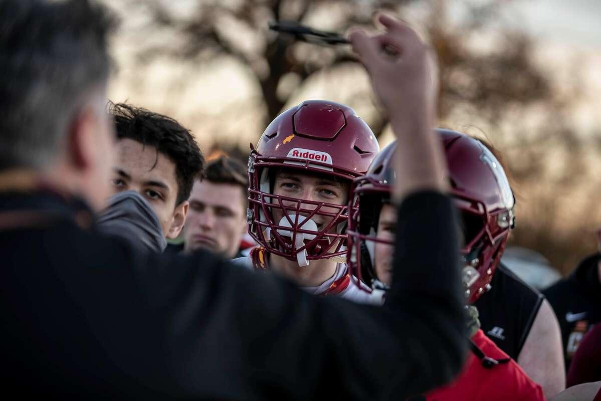 Members of the Cardinal Newman High School varsity football team listen as head coach Paul Cronin speaks after a practice in Santa Rosa, California Thursday, Mar. 11, 2021.