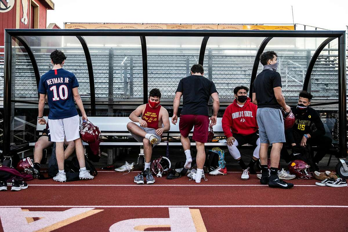Members of the Cardinal Newman High School varsity football team prepare to leave the field after practice in Santa Rosa, California Thursday, Mar. 11, 2021.