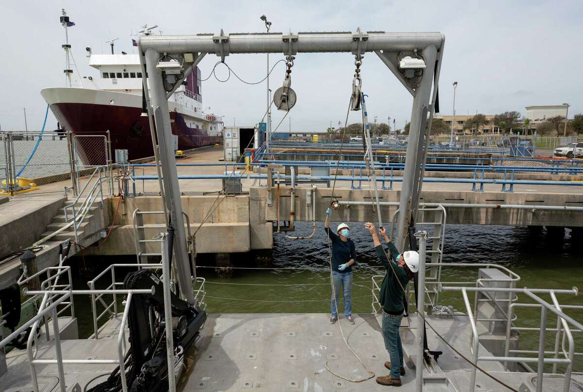 Karol Breuer, center, and Justin Blake, right, first mate and captain of Research Vessel Manta respectively, work to feed a science winch cable through a pulley that's part of the boat, which helps maintain the Flower Garden Banks National Sanctuary, on Thursday, March 11, 2021, in Galveston, Texas. The sanctuary is an underwater national park that protects some coral right now. New protections for coral reefs in the Gulf Coast are expected to take effect in the next few weeks.
