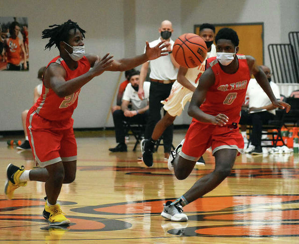 Alton's Ihzel Brown (left), and Byron Stampley head up the court after getting a steal at midcourt in a Southwestern Conference Tournament first-round game against Edwardsville on Thursday night at Lucco-Jackson Gym in Edwardsville.