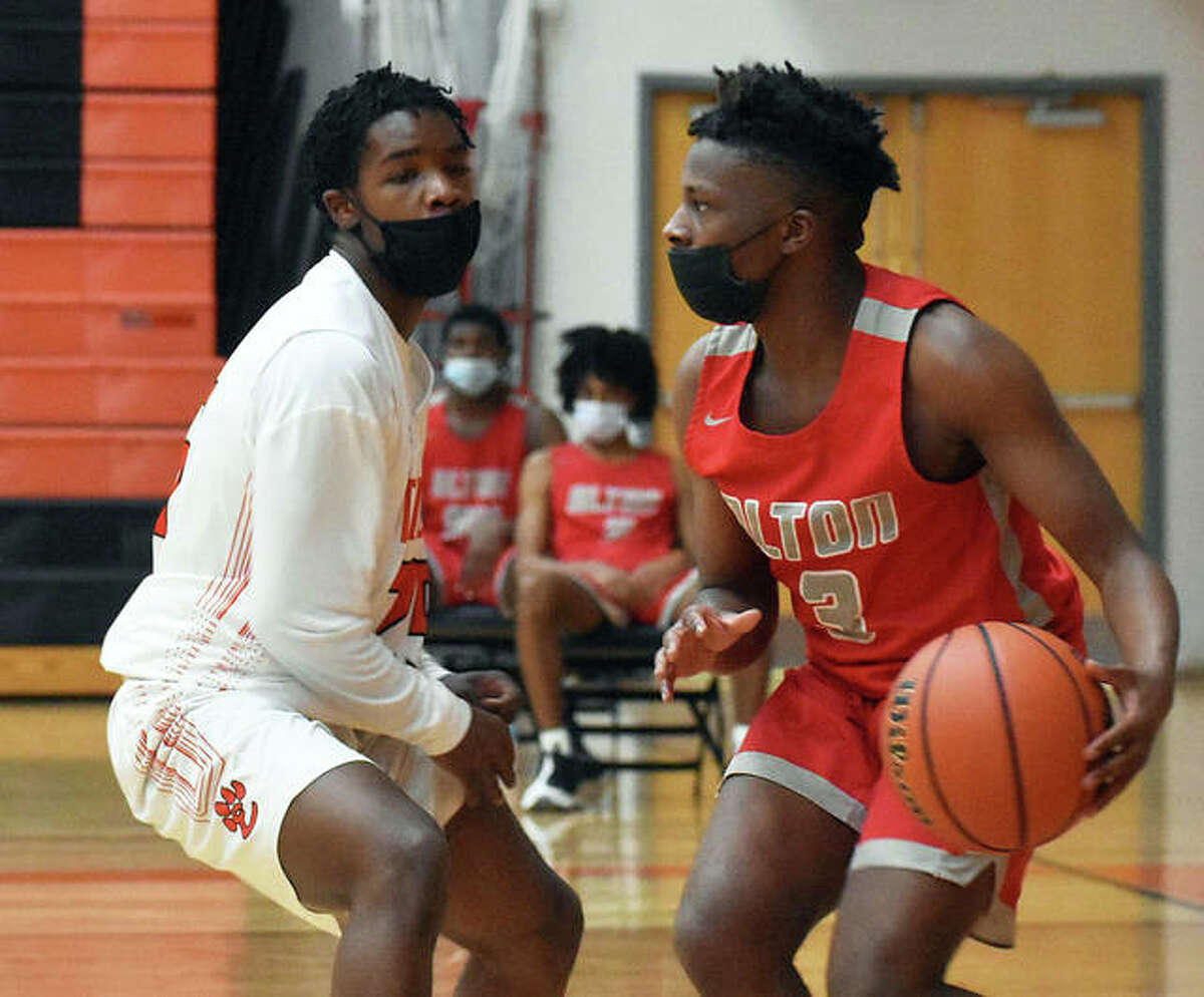 Alton's Keith Smith (right) looks for an open teammate with Edwardsville's Gabe James defending him in the fourth quarter Thursday night in Edwardsville.