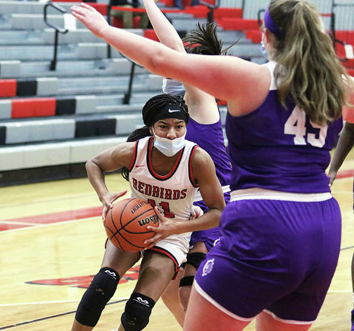 Alton's Renee Raglin (left) takes the ball to the basket against Collinsville defenders in a Feb. 23 SWC game at Alton High in Godfrey. On Thursday, Raglin scored 13 points to lead the Redbirds in a season-ending loss at Belleville West in the SWC Tourney.