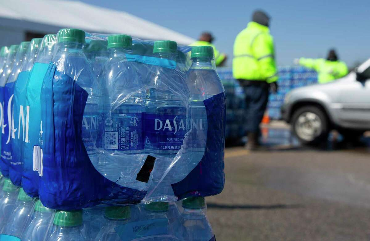 Houston residents wait in line to get free bottled water at a mass distribution Feb. 19 at Delmar Stadium.