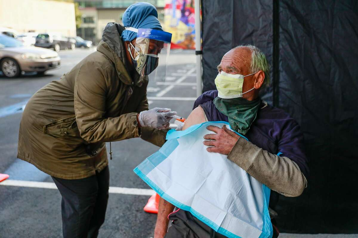 Nurse Sonni Belcher-Collins administers a dose of the Johnson & Johnson COVID-19 vaccine to Doug Rosen in Oakland. The Trust Health Center hosted a mass vaccination day for people who are unhoused, housing insecure or staff members of the clinic.