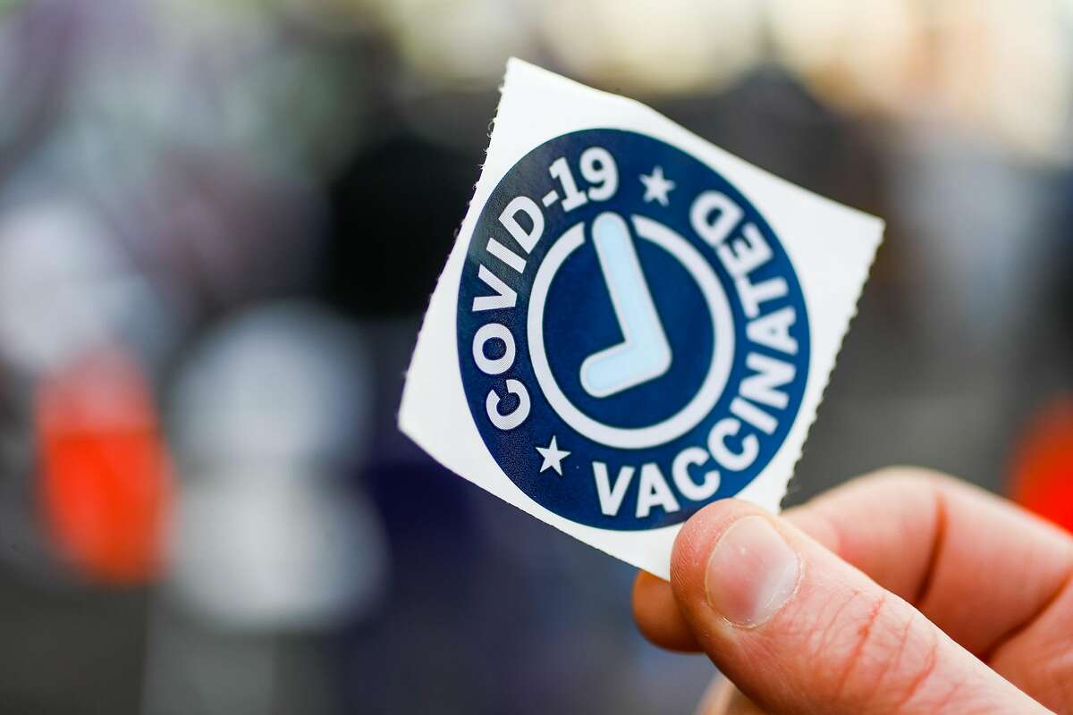 A woman shows the sticker given to people who received COVID-19 vaccinations in Oakland.
