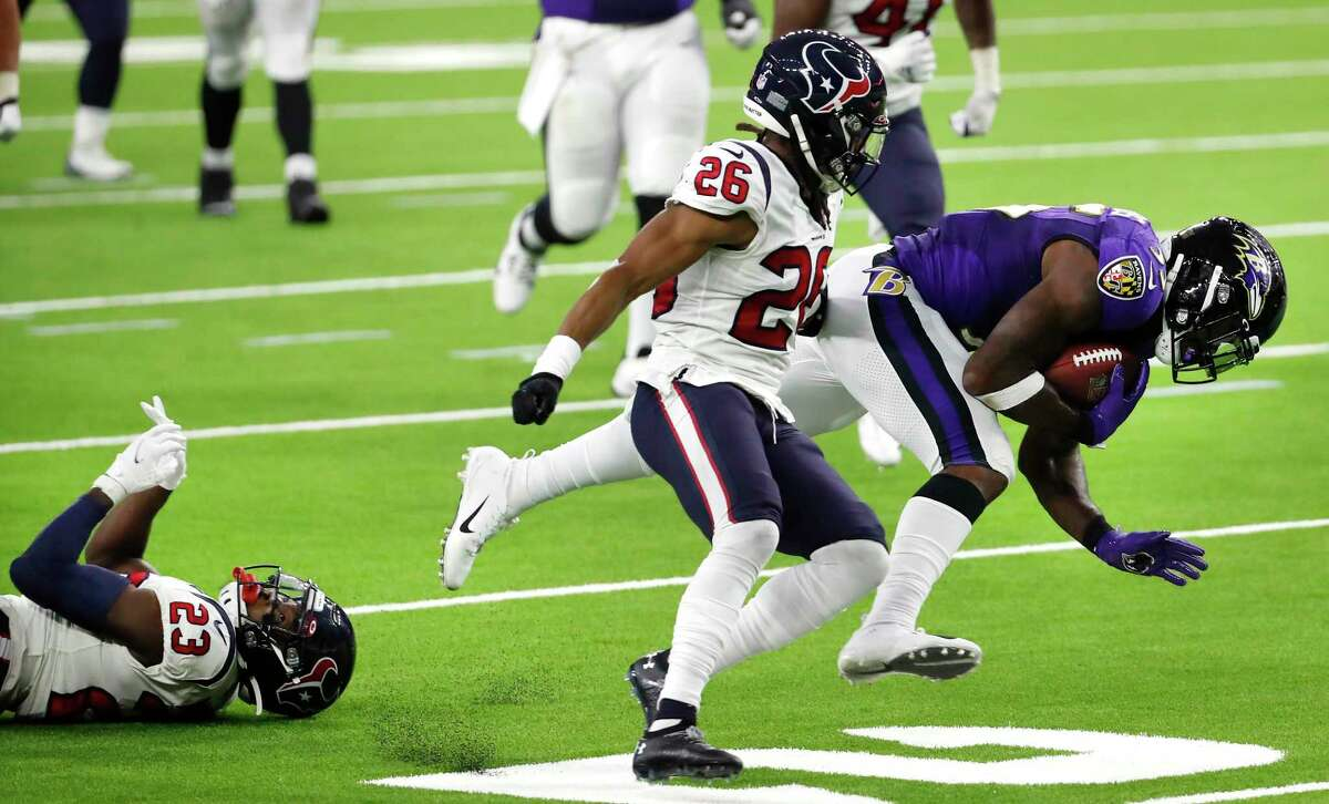Baltimore Ravens running back Gus Edwards (35) breaks away from Houston Texans strong safety Eric Murray (23) and cornerback Vernon Hargreaves III (26) during the second half of an NFL football game at NRG Stadium on Sunday, Sept. 20, 2020, in Houston.