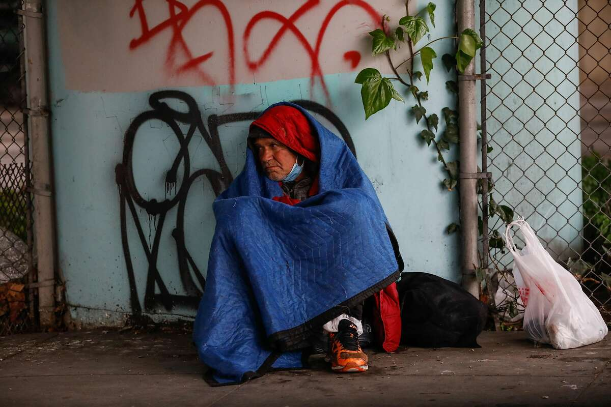 A homeless man takes cover under the freeway during a rainstorm on Market Street on Thursday, Feb. 11, 2021 in San Francisco, California.