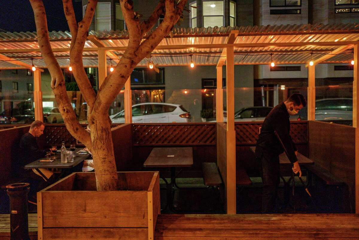 Ronnie Selak sweeps the parklet at Brazen Head just before the mandatory 10pm curfew takes effect in San Francisco on Monday, November 30, 2020.