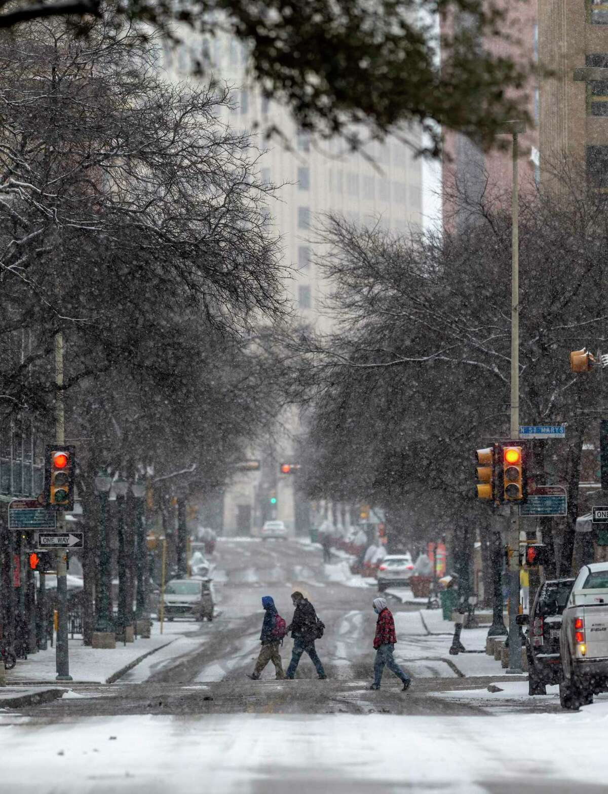 People cross Houston Street Thursday, Feb. 18, 2021 as snow grips the city for the second time in a week, the result of an arctic air mass that sent temperatures plummeting and resulted in rolling blackouts. At one point about 1/3 of all CPS Energy customers were without electricity.