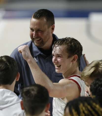 Huffman's Jacob Harvey (10) celebrates beside head coach Scott Barrett after defeating Boerne 55-49 during a Class 4A state semifinal game at Delmar Fieldhouse, Tuesday, March 9, 2021, in Houston. Photo: Jason Fochtman/Staff Photographer / 2021 © Houston Chronicle