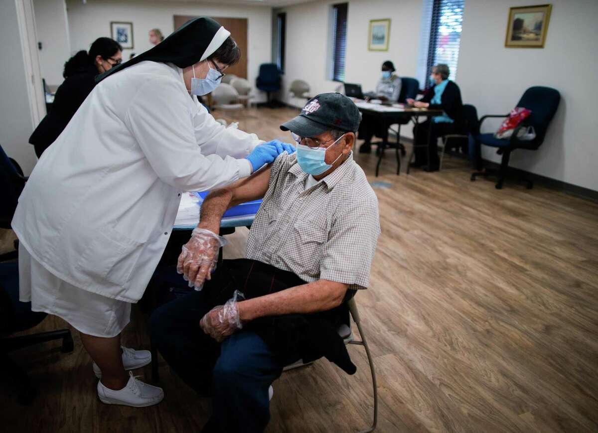 Benito Moreno, 77, gets an adhesive bandage after being vaccinated with the COVID-19 second dose of Moderna at the CHRISTUS St. Mary's Clinic, Thursday, March 11, 2021, in Houston.