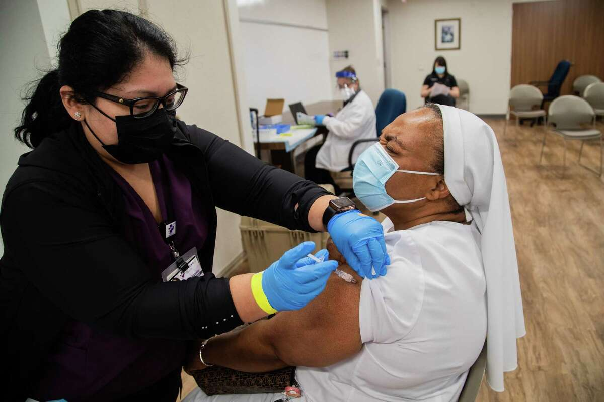Sister Veronica Ogunlade, 49, closes her eyes as she gets the first Moderna COVID-19 vaccine at the CHRISTUS St. Marys Clinic, Thursday, March 11, 2021, in Houston.