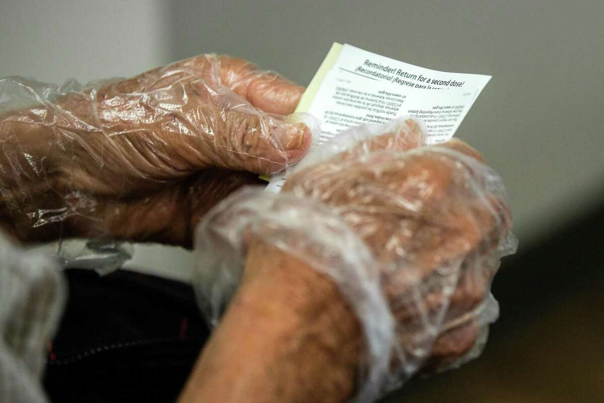 Benito Moreno, 77, holds his COVID-19 vaccination record card after receiving the COVID-19 second dose of Moderna at the CHRISTUS St. Mary's Clinic, Thursday, March 11, 2021, in Houston.