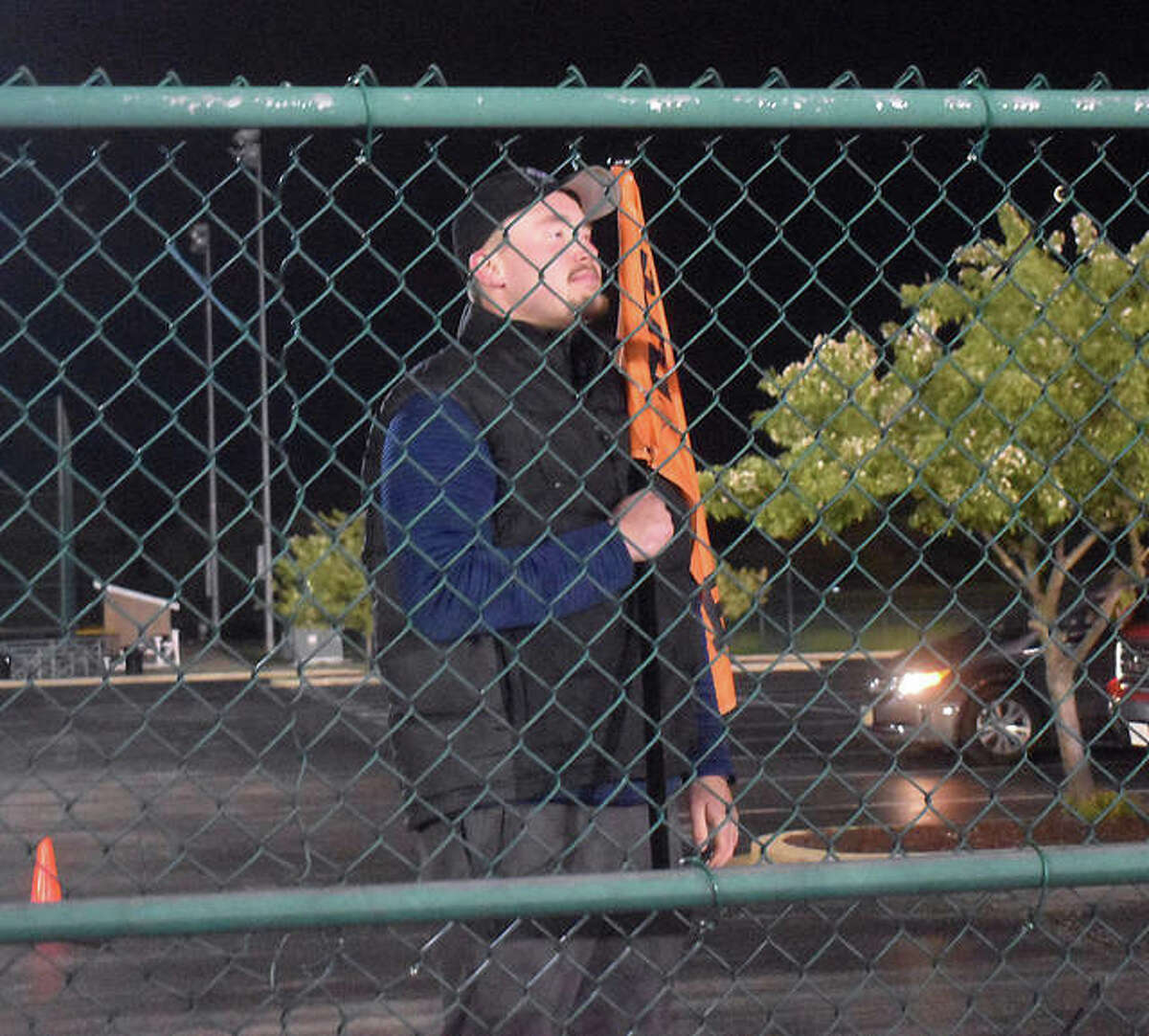 Edwardsville senior Jacob Kitchen looks at the football field from behind the gate in the parking lot in April. The Southwestern Conference schools lit up football fields and baseball stadiums at 20:20 military time on a Friday night in April in honor of the 2020 class.