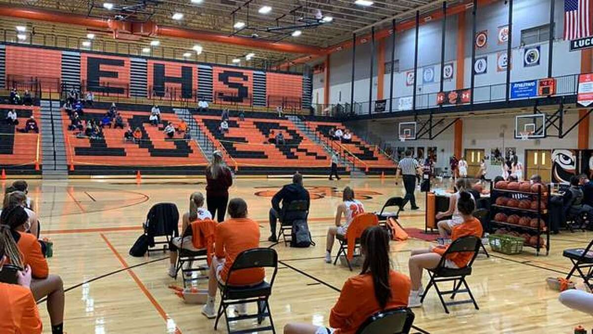 The Edwardsville girls basketball team sits spread out on the sideline to allow for social distancing in the return to the court on Feb. 6. Fans were seated 30 feet away from the court and spread out, as well.