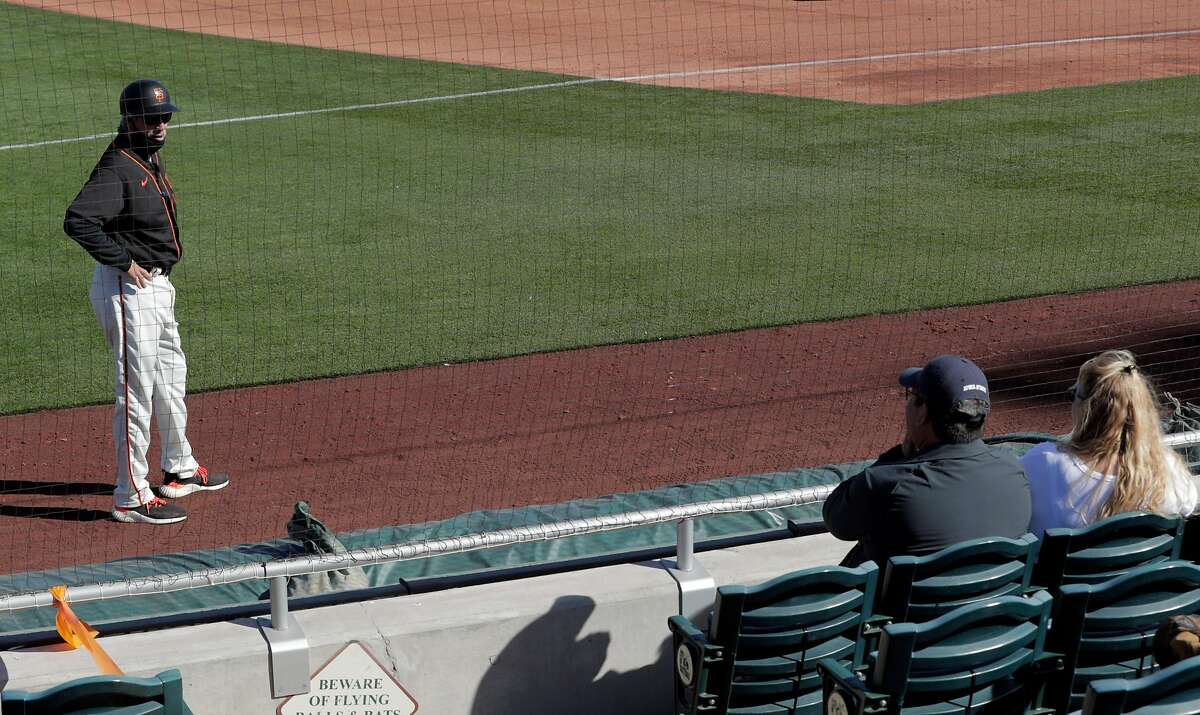 Giants third base coach Ron Wotus talks to fans from a distance as the San Francisco Giants played the Los Angeles Angels at Scottsdale Stadium in Scottsdale, Ariz., on Sunday, February 28, 2021.