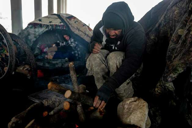 Victor Carrizales, 41, arranges logs inside his fire pit to keep him and others warm as the cold weather descended on San Antonio in February. Hester huddled in her tent behind him, avoiding the heavy smoke from the fire. Photo: Jessica Phelps /San Antonio Express-News / **MANDATORY CREDIT FOR PHOTOG AND SAN ANTONIO EXPRESS-NEWS/NO SALES/MAGS OUT/TV  © 2021 San Antonio Express-News