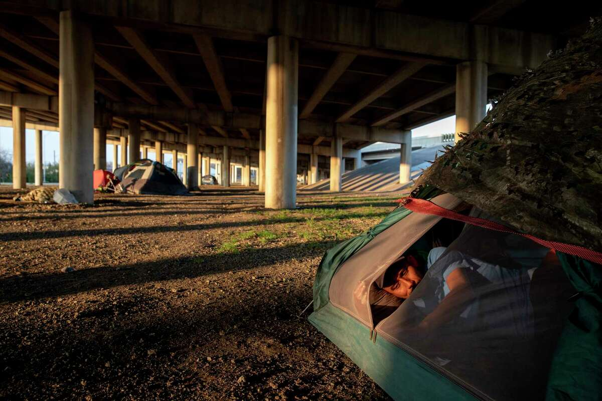 As the evening sun sets, Richie Garcia rests in his tent under the I-37 overpass. The camp had been cleared by city officials the week before, but the number of people setting up their tents has been growing again.