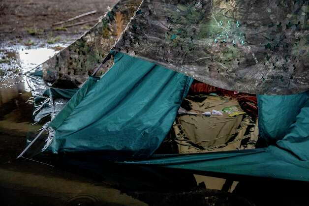 Heavy rains flooded the camp under the overpass as the deadly winter storm crept toward Texas, soaking blankets and making it hard to stay warm and dry. Photo: Jessica Phelps /San Antonio Express-News / **MANDATORY CREDIT FOR PHOTOG AND SAN ANTONIO EXPRESS-NEWS/NO SALES/MAGS OUT/TV  © 2021 San Antonio Express-News