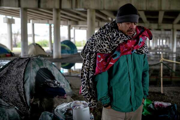 David Castillo huddles in a blanket under the I-37 overpass. Temperatures inched just above freezing after the sun rose.