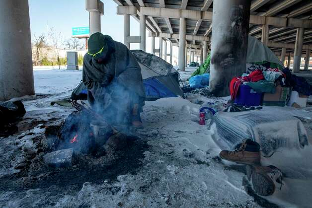 A man who goes by the name 'Snipe' tries to keep warm a the fire. Despite temperatures hitting the single digits, many unsheltered people like Snipe decided to stay put instead of seeking emergency shelter indoors. Photo: Jessica Phelps /San Antonio Express-News / **MANDATORY CREDIT FOR PHOTOG AND SAN ANTONIO EXPRESS-NEWS/NO SALES/MAGS OUT/TV  © 2021 San Antonio Express-News