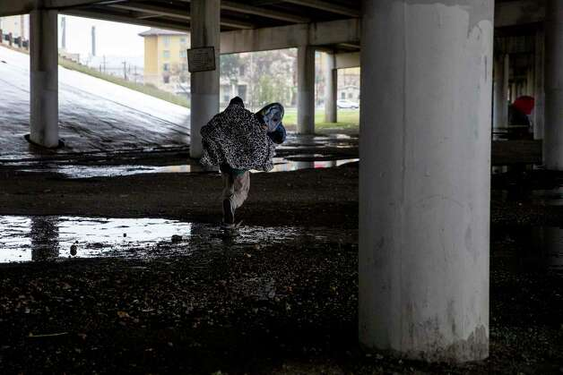 David Castillo hauls blankets donated by volunteers to his tent under the I-37 overpass. Photo: Jessica Phelps /San Antonio Express-News / **MANDATORY CREDIT FOR PHOTOG AND SAN ANTONIO EXPRESS-NEWS/NO SALES/MAGS OUT/TV  © 2021 San Antonio Express-News