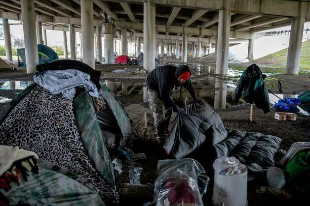 Victor Carrizales tries to dry out his sleeping bag after his tent flooded in a rainstorm that flooded the camp under the I-37 overpass. Photo: Jessica Phelps /San Antonio Express-News / **MANDATORY CREDIT FOR PHOTOG AND SAN ANTONIO EXPRESS-NEWS/NO SALES/MAGS OUT/TV  © 2021 San Antonio Express-News