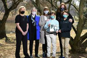 From left, Lisa Beeson, Joan Andrews, Amanda Vigale, Oliver Vigale, 11, Stephanie Karp, and Major Karp, 12, pose with a photo of Carolyn Tarpey and her 14-year-old son, Henry, at Bruce Park in Greenwich, Conn. Thursday, March 11, 2021. Tarpey was diagnosed with esophageal cancer three months ago and then contracted COVID-19 in February. Carolyn is currently at Yale New Haven Hospital in a medically induced coma on a ventilator. Her friends started a GoFundMe campaign that has raised close to $100,000 to support the costs of her medical care and her 14-year-old son, Henry.